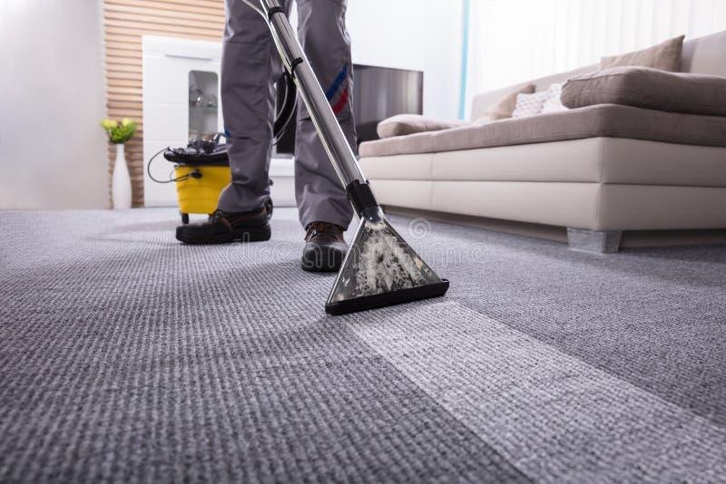 Líquido de limpeza de Person Cleaning Carpet With Vacuum fotografia de stock royalty free