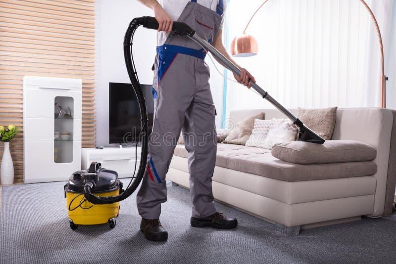 Líquido de limpeza de Person Cleaning Sofa With Vacuum foto de stock