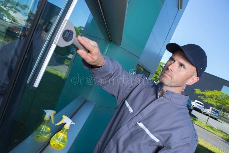 Líquido de limpeza profissional que swiping a janela no local fotos de stock