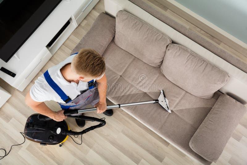 Líquido de limpeza Sofa With Vacuum Cleaner do homem novo imagem de stock royalty free