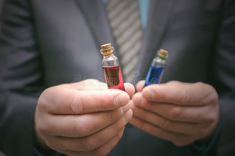 Líquido esencial de la píldora azul y roja en manos del hombre de negocios Opción correcta de medicamentos fotografía de archivo