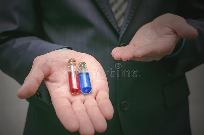Líquido essencial do comprimido azul e vermelho nas mãos do homem de negócio Escolha do comprimido direito foto de stock