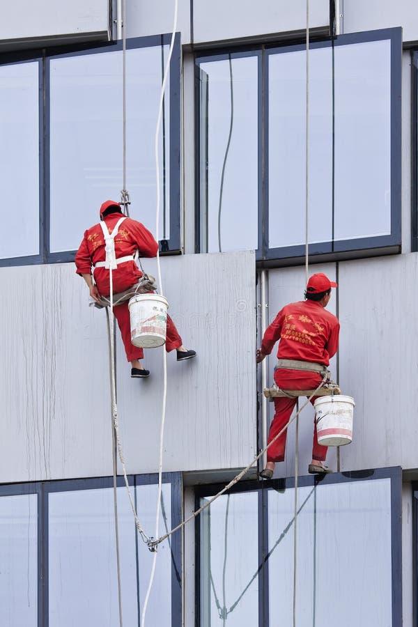 Líquidos de limpeza de janela que penduram em cordas contra um prédio de escritórios, Pequim, China foto de stock