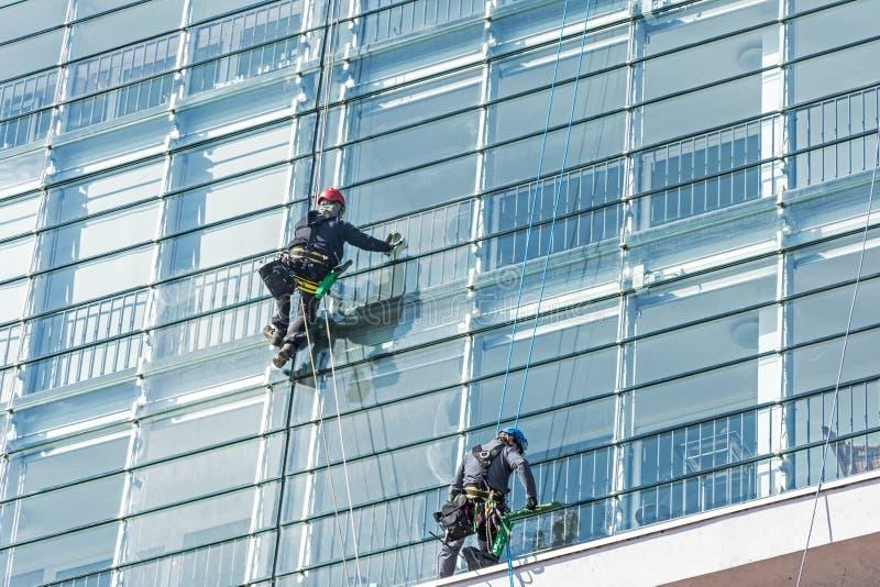 Líquidos de limpeza de janela na fachada de vidro de um arranha-céus fotos de stock
