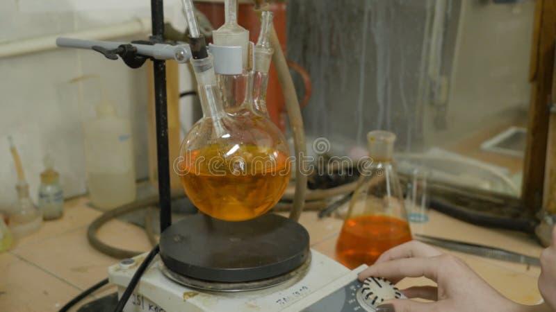 Líquidos de mezcla del científico en frascos en un laboratorio de investigación Equipo especial para los líquidos de mezcla en la foto de archivo
