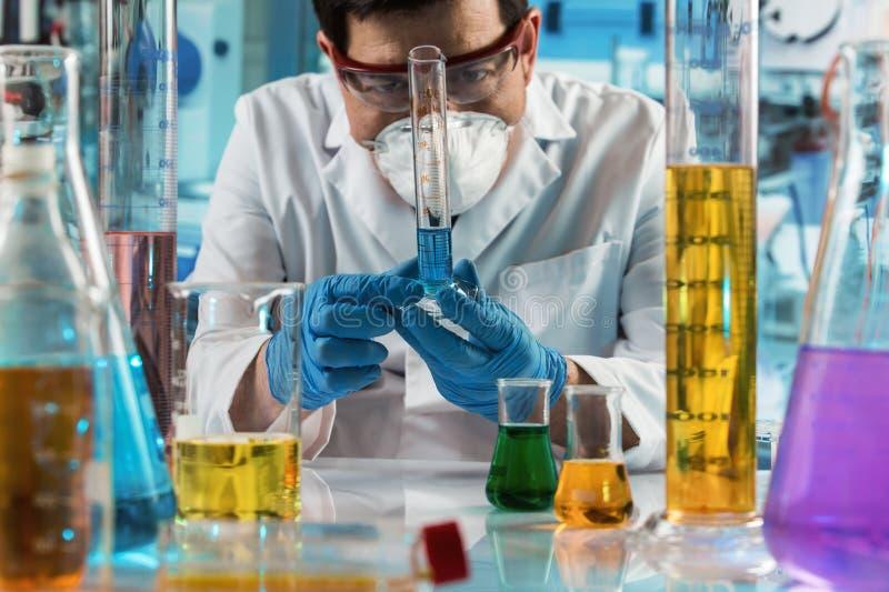 Líquidos de mezcla del investigador con un tubo de ensayo y un frasco para la prueba de laboratorio fotos de archivo libres de regalías