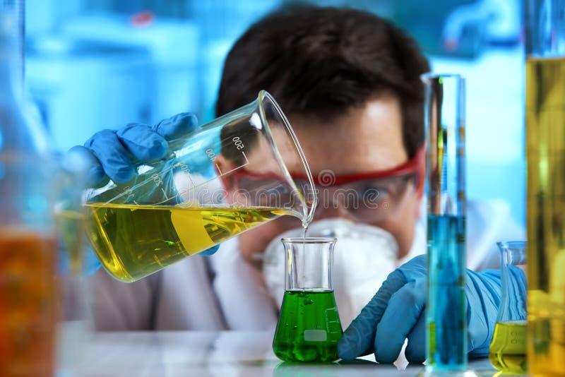 Líquidos de mistura de trabalho do pesquisador no laboratório da bioquímica fotografia de stock