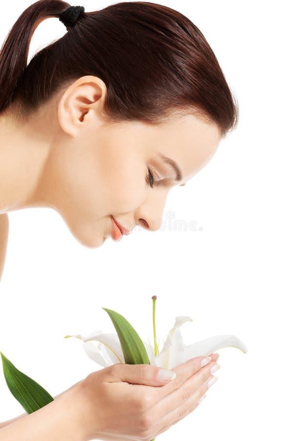 Lírio branco de cheiro da jovem mulher fotos de stock royalty free