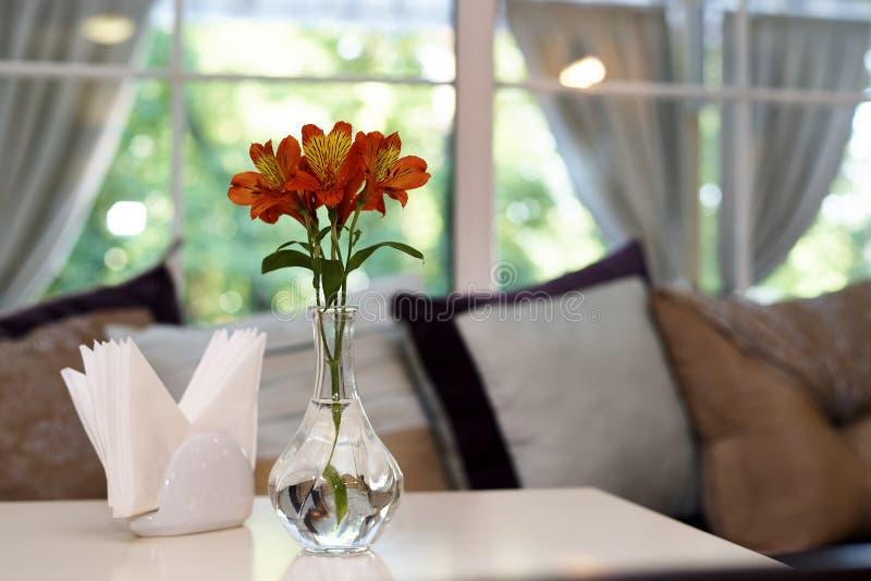Lírios frescos em um vaso de vidro com água em uma tabela fotos de stock royalty free