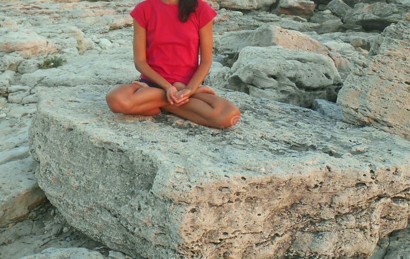 Lótus de formação da ioga da menina com os pés descalços em um fundo das pedras imagens de stock royalty free