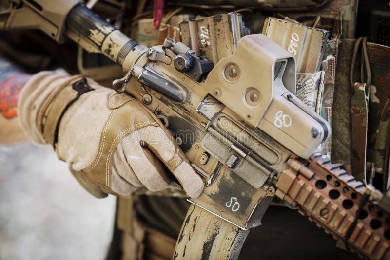 Lödmetall i handskar som rymmer det automatiska geväret för anfall fotografering för bildbyråer