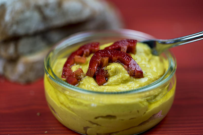 Löffel in Curry hummus mit Peperonischeiben stockfotos