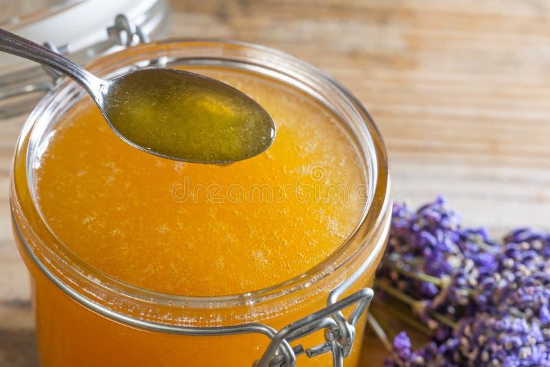 Löffel des Honigs und des Glases mit Honig stockbild