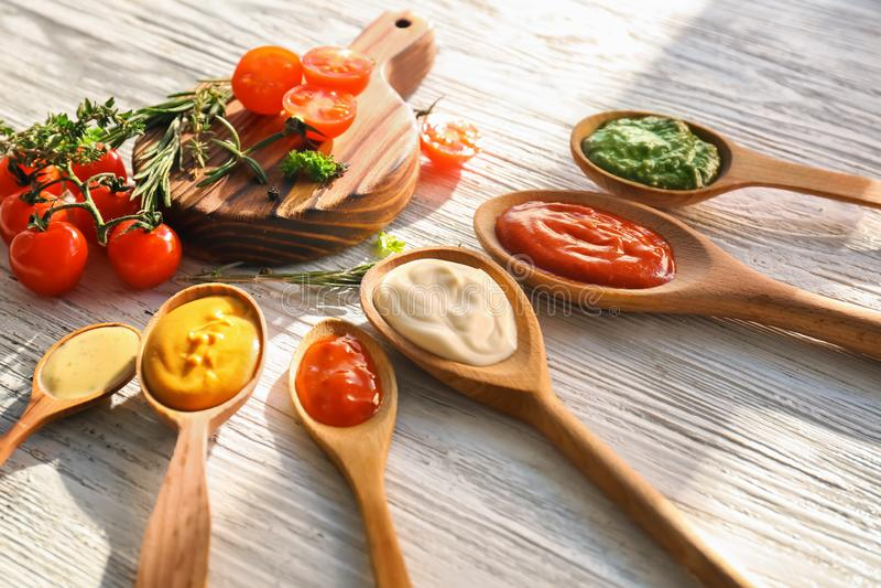 Löffel mit geschmackvollen Soßen auf weißem Holztisch stockfotografie