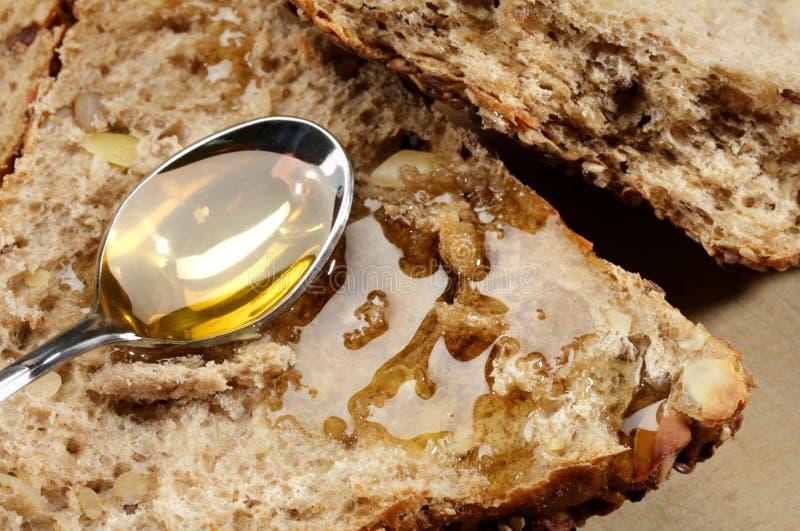 Löffel mit Honig und Brot lizenzfreie stockfotos