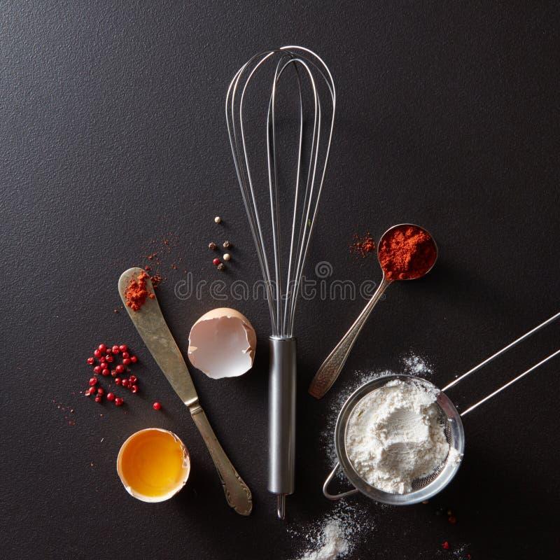 Löffel mit rotem Pfeffer, Metallschneebesen, rohem Ei des Weinlesemessers und Mehl auf einem schwarzen konkreten Hintergrund mit  stockfotografie