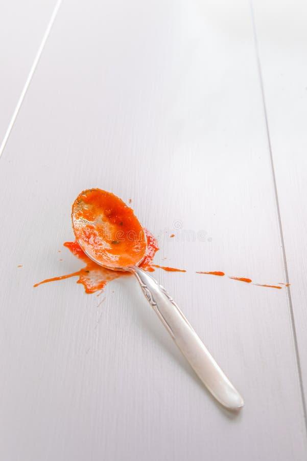 Löffel mit Tomatensaucespritzen auf weißer Tabelle stockfotografie