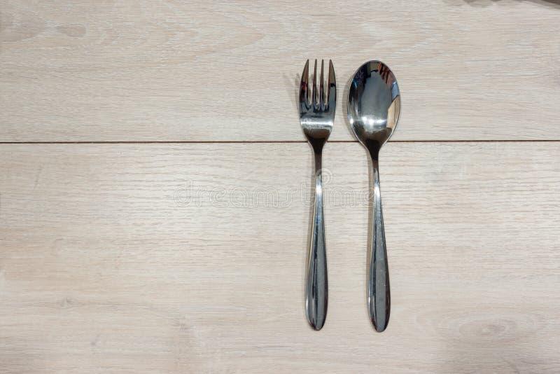 Löffel und Gabel auf einem Holztisch lizenzfreies stockfoto