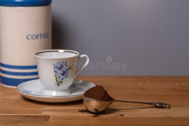Löffel von geerdeten Kaffeebohnen auf Holztisch stockfotografie