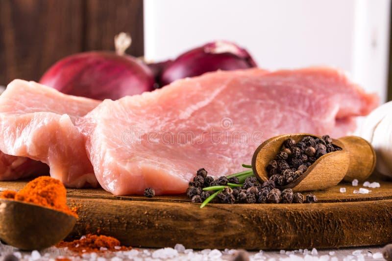 Löffeln Sie voll von pepprer Samen nahe bei rohem Schweinefleisch stockbild