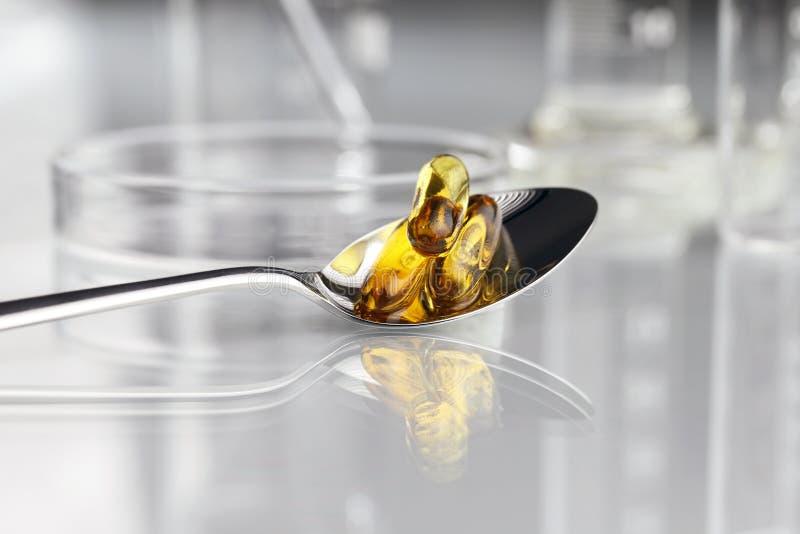 Löffelvitaminpillen Omega 3 Ergänzungen mit Petrischale lizenzfreies stockbild
