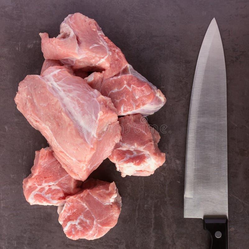 Lögner för nytt rått kött och för en slaktarekniv på yttersidan av ett mörker fotografering för bildbyråer