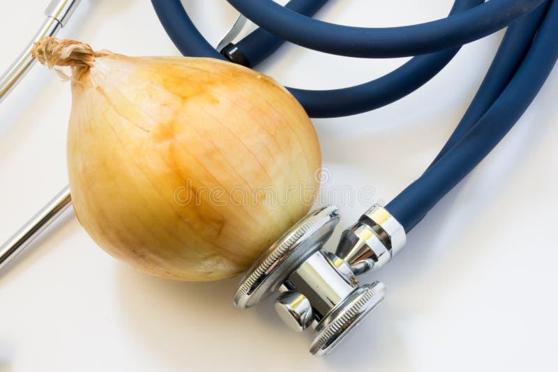 Lök och stetoskop Stetoskopet testar löken för närvaro av GMO, sjukdomar av grönsaken, variationer Näring och vård- fördel royaltyfria bilder