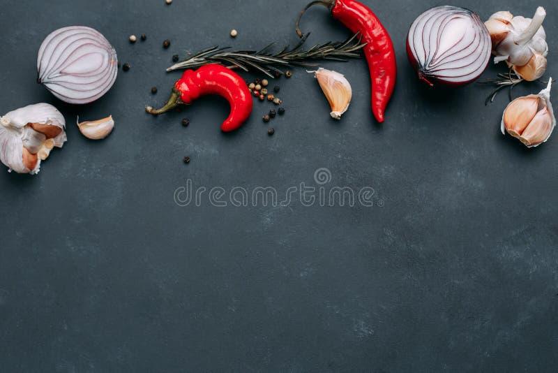 Lökar, chilipeppar, vitlök, örter och kryddor på mörk tabell, K fotografering för bildbyråer