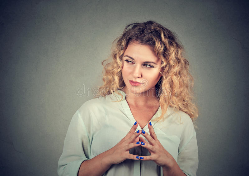 Lömsk, slug beräknande ung kvinna som konspirerar något fotografering för bildbyråer
