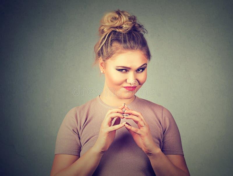 Lömsk, slug beräknande ung kvinna som konspirerar något Negativa mänskliga sinnesrörelser, ansiktsuttryck royaltyfri fotografi