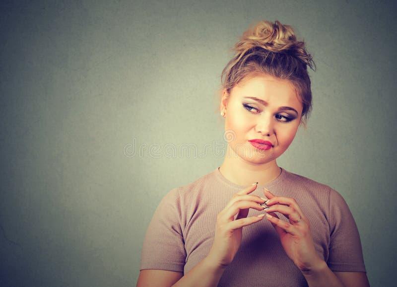 Lömsk, slug beräknande ung kvinna som konspirerar något Negativa mänskliga sinnesrörelser, ansiktsuttryck arkivbilder