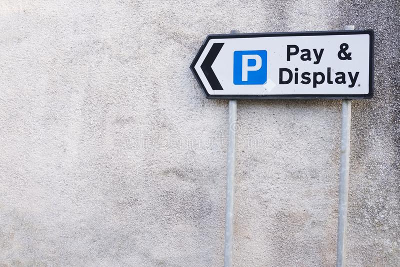 Lön- och skärmtecken som pekar pilen till den utomhus- parkeringshuset för att undvika en bot eller en biljett arkivfoto