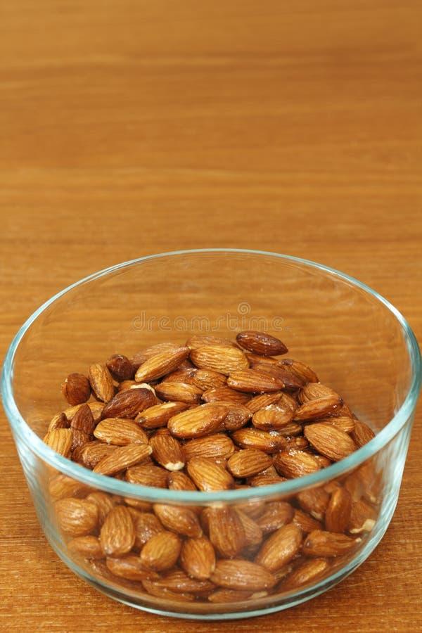 Lönn glasade mandlar i en Glass bunke fotografering för bildbyråer