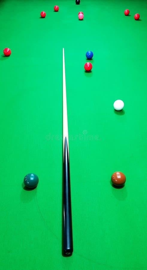 Lönn och ebenholtssvart stickreplik på en snookertabell med bollar royaltyfria foton