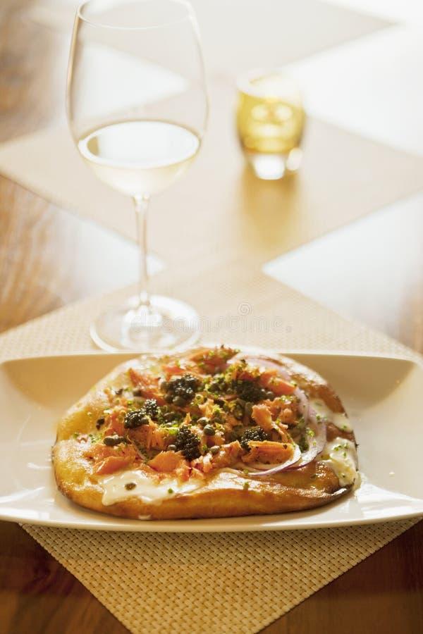 Lönn-rökt laxpizza och exponeringsglas av vin royaltyfri foto