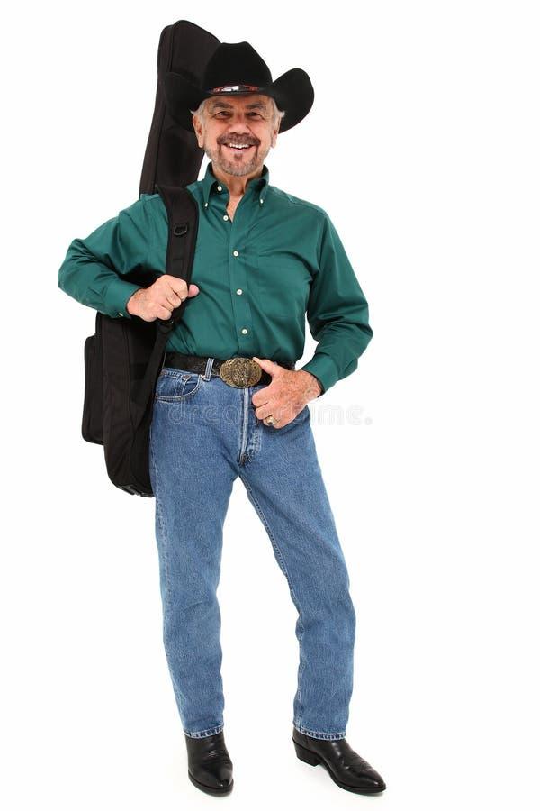 Löpande gammalare man för musiker med gitarren royaltyfri foto