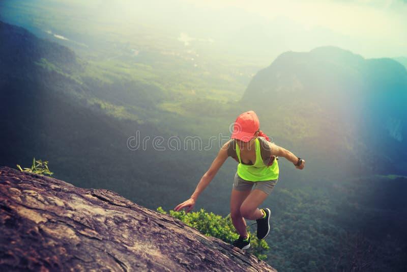 löpare för konditionkvinnaslinga som upp till kör bergöverkanten fotografering för bildbyråer
