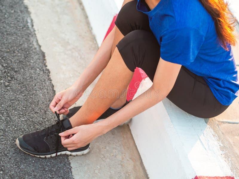 Löpare för ung kvinna som binder skosnöret, innan att köra arkivbild