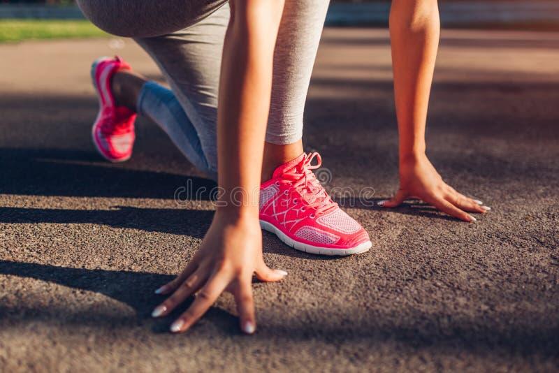 Löpare för ung kvinna som får av till en tidig start på sportsground i sommar Slut upp av gymnastikskor och händer royaltyfria foton