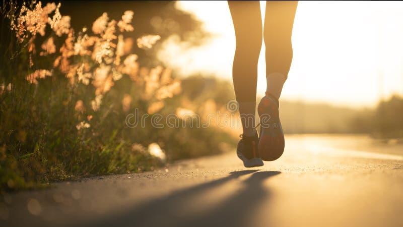 Löpare för ung kvinna som kör på stadsbrovägen, ung idrottsman nen för konditionkvinnalöpare som kör på vägen fotografering för bildbyråer