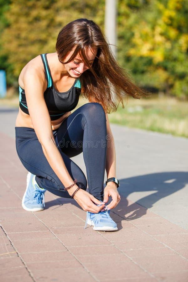 Löpare för ung kvinna som snör åt upp skosnöre på slinga royaltyfria foton