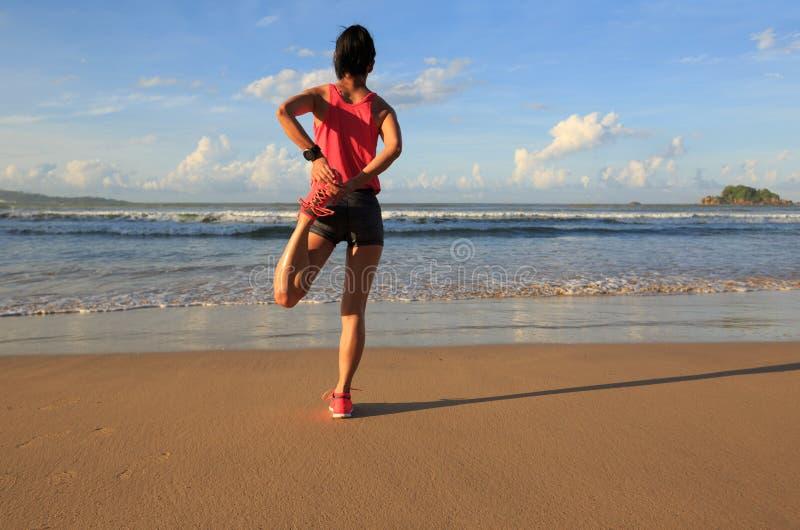 löpare för ung kvinna som sträcker ben, innan att köra på soluppgångsjösidan royaltyfri bild
