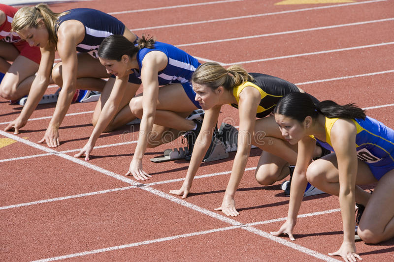 Löpare som förbereder sig för lopp på startgrop royaltyfria bilder