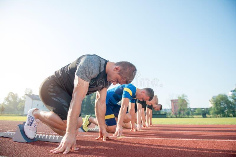 Löpare som förbereder sig för lopp på startgrop royaltyfri foto