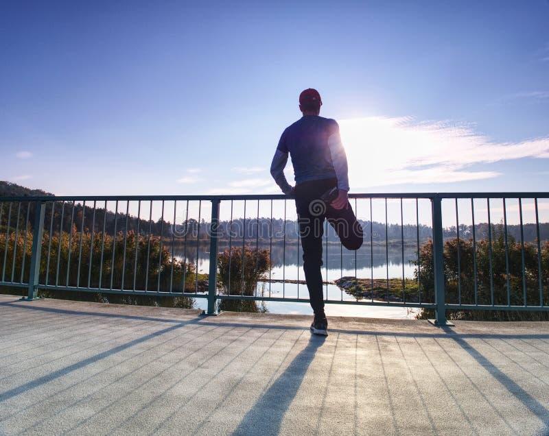 Löpare som gör sträcka övning på bron En aktiv seg man arkivfoto