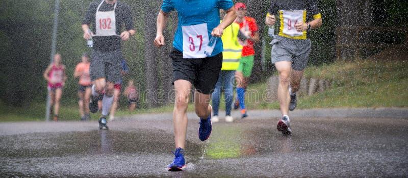 Löpare som kör under maraton för regndroppstad arkivbilder