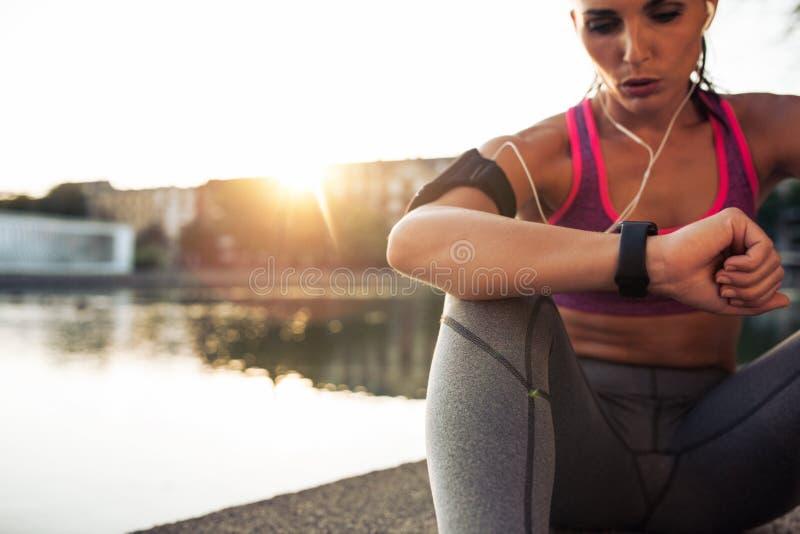Löpare som kontrollerar hennes kapacitet på den smarta klockaapparaten för kondition royaltyfri bild