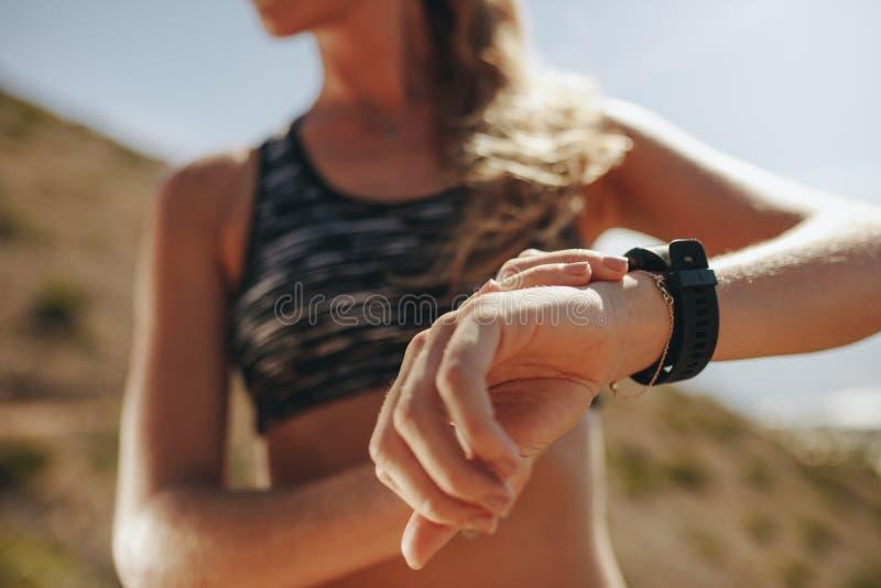 Löpare som kontrollerar konditionframsteg på hennes smarta klocka royaltyfri foto