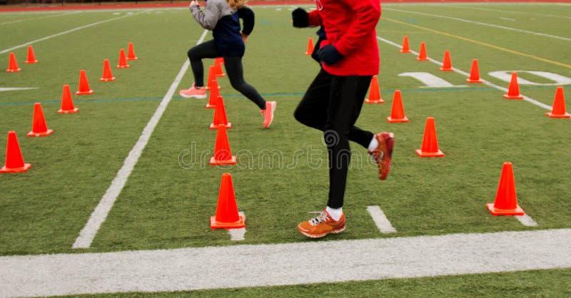 Löpare som utbildar över orange kottar royaltyfri bild