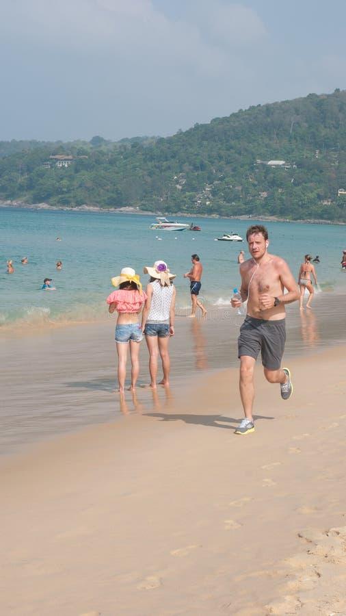 Löpare - ung man som joggar på stranden royaltyfri foto